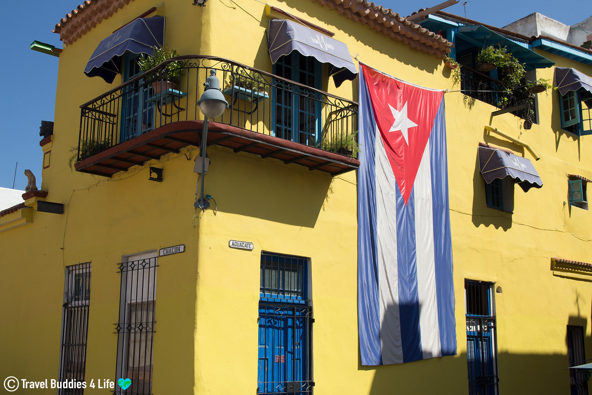 A Yellow House With A Cuba Flag In Havana, Cuba Haggling