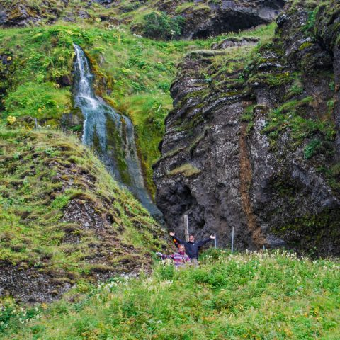 Ali and Joey Standing with a Small Icelandic Waterfall