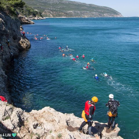 Coasteering Group in the Water Swimming to the Next Cliff Jumping Location in the Arrábida Nature Park