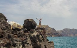 Nadine Climbing On The Rocks At Amoudi Bay, Santorini