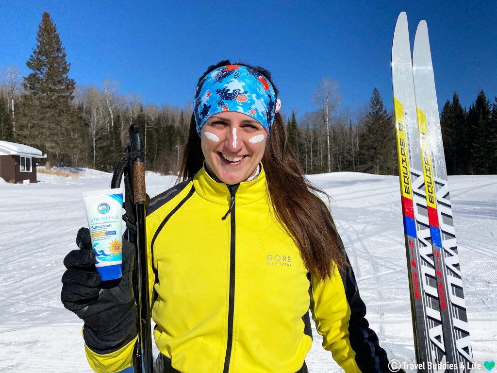 Nadine Holding Stream2Sea's Reef Safe Sunscreen on the Ski Slopes