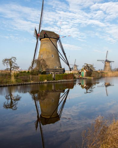 The Reflection Of A Kinderdijk Windmill In The Netherlands