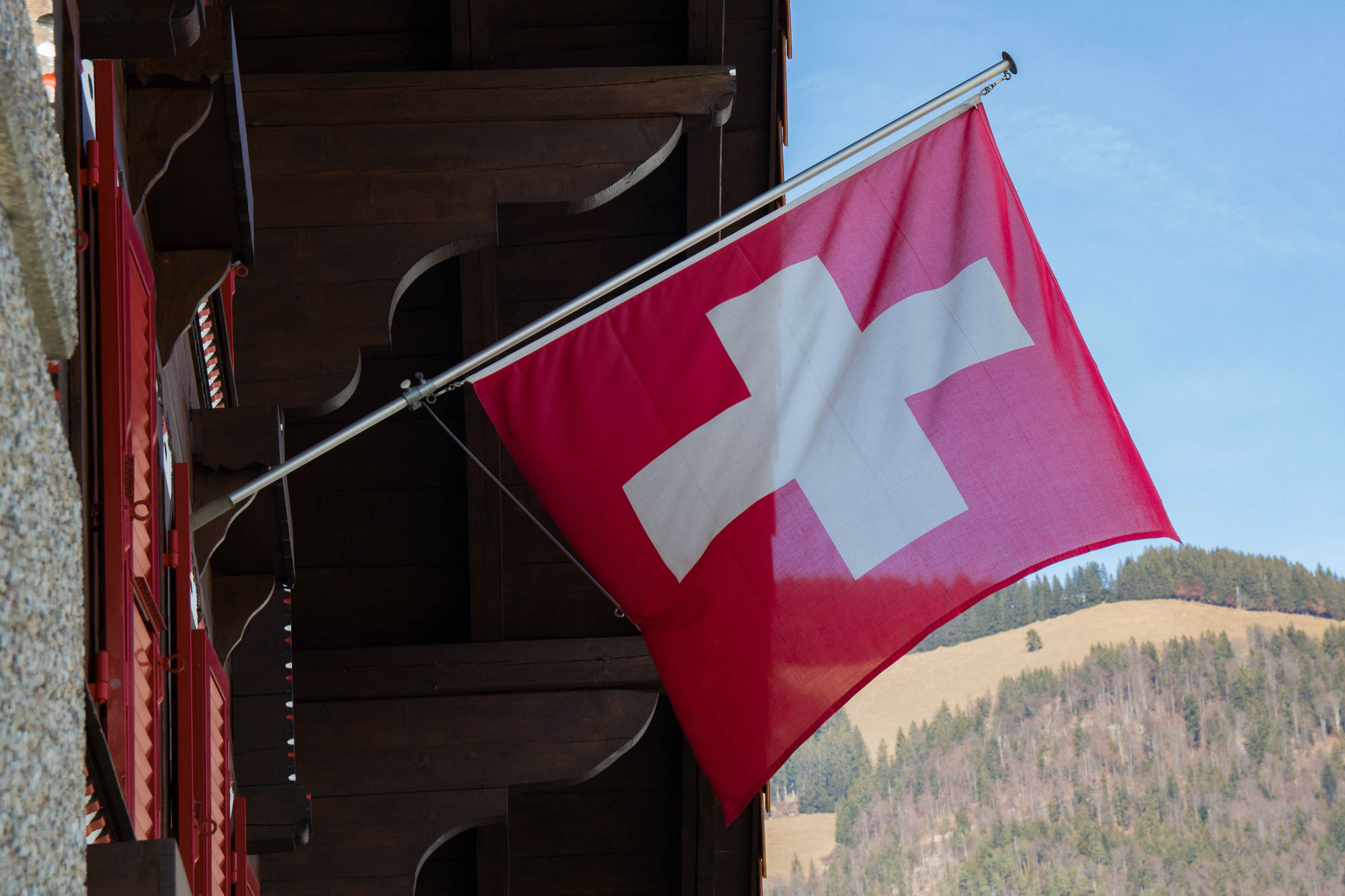 The Switzerland Flag With Mountains In The Background